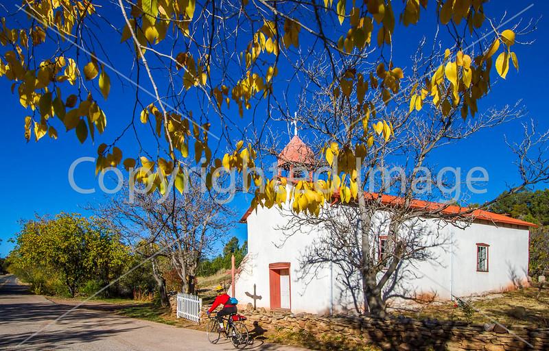 Cyclist passing historic Catholic church in Apache Canyon, NM - D4-C2-0328 - 72 ppi