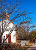 Cyclist passing historic Catholic church in Apache Canyon, NM - D4-C3-0248 - 72 ppi