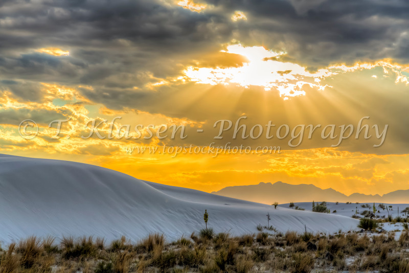 A sunburst through the clouds at the White  Sands National Monument at sunset near Alamogordo, New Mexico, USA.