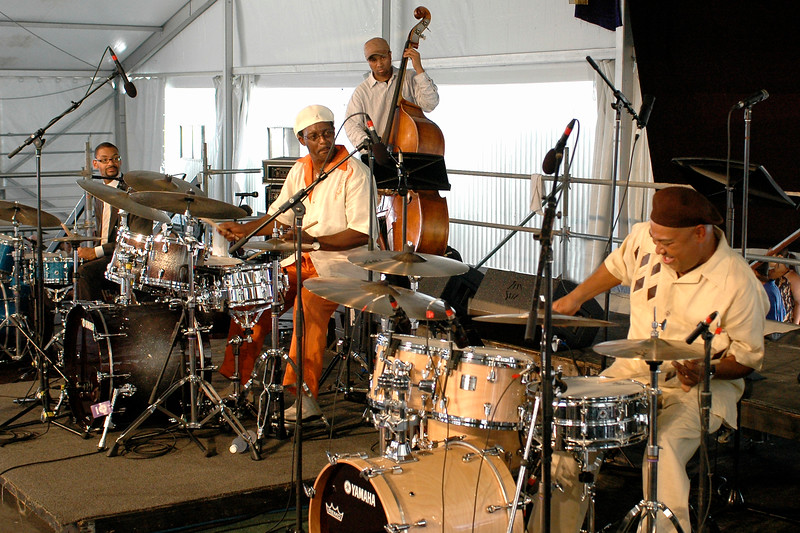 Jason Marsalis, Herlin Riley and Shannon Powell performing live on stage as part of the Max Roach Tribute at the New Orleans Jazz & Heritage Festival on May 4, 2008.  They are joined by bassist Roland Guerin.