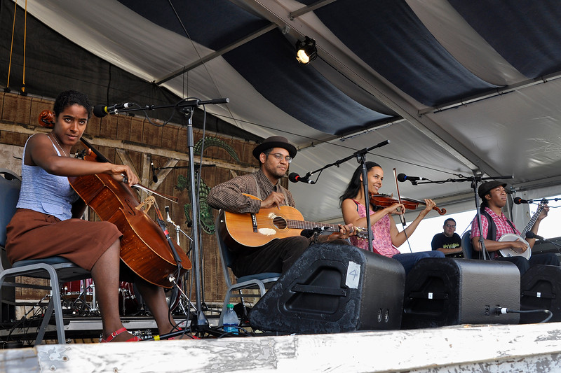NEW ORLEANS, LA-APRIL 28: Carolina Chocolate Drops perform at the New Orleans Jazz & Heritage Festival in New Orleans, LA on April 28, 2012. (L-R): Leyla McCalla, Dom Flemons, Rhiannon Giddens, Hubby Jenkins (Photo by Clayton Call/Redferns)