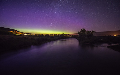 The Aurora Borealis lights up the night sky as seen from the Saint Mary River in Glacier National Park, Montana.