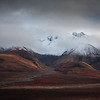 Snow graces the mountain peaks as the tundra below is ablaze in its autumn splendor in Denali National Park, Alaska.
