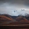 Snow graces the mountain peaks as the tundra below is ablaze in its autumn splendor in Denali National Park, Alaska.