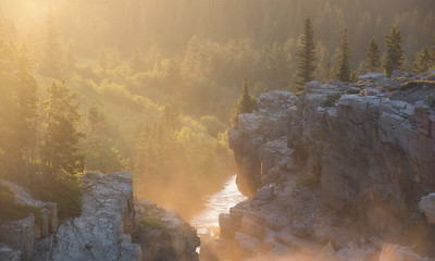 Fog lifts from the tailwaters of Swiftcurrent Lake during sunrise in Glacier National Park, Montana.