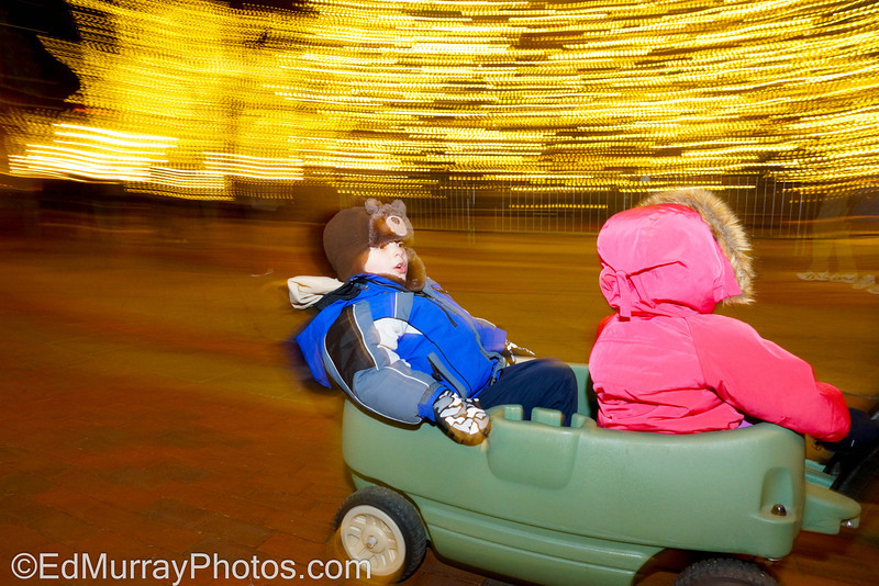 Rocket Around the Christmas Tree: If it's ok with everyone, I'd like to add some shot along with the elf series....this one is of the boy and his cousin racing by the Quincy Market Christmas Tree in Boston...kind of a weird shot. I'm not sure if I should keep it or not. Any thoughts?  12/19/12