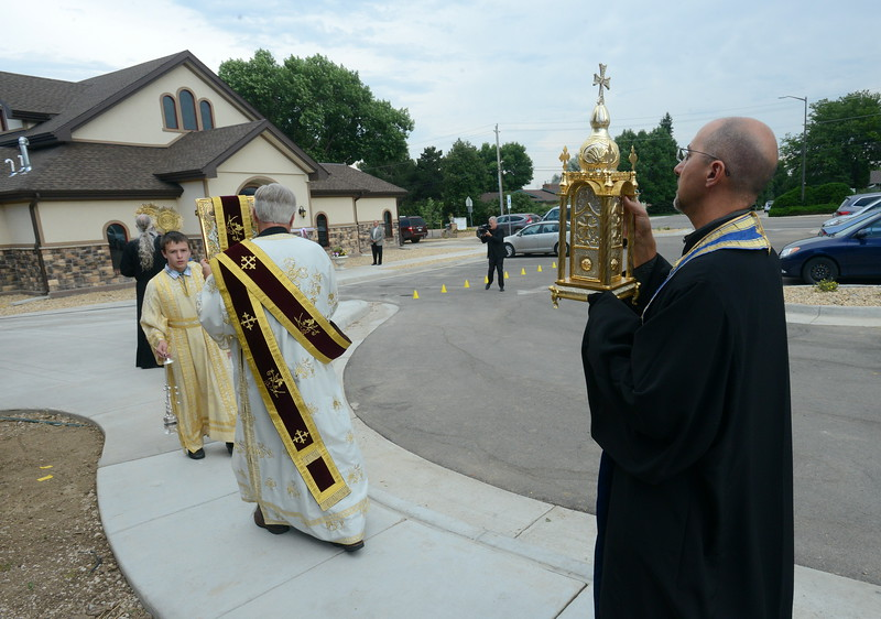 The Rev. Evan Armatas, the priest of St. Spyridon Orthodox Church in Loveland, carries the tabernacle from the church's gym, where the congregation worshiped for a  year during construction work, to the newly renovated church on Saturday evening, Aug. 4, 2018. In front of him, a procession of altar servers and Deacon Mark O'Dell carry the altar light, incense, cross and Gospel book. (Photo by Craig Young / Loveland Reporter-Herald)