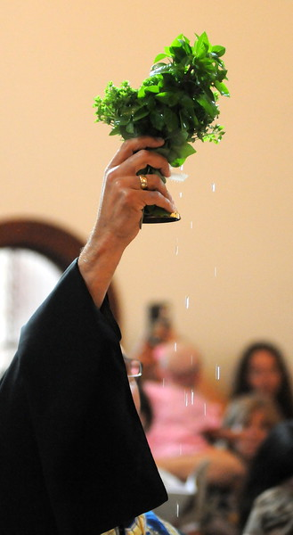 Holy water drips from a cross and clump of basil that the Rev. Evan Armatas holds aloft during a blessing ceremony Saturday, Aug. 4, 2018, for St. Spyridon Orthodox Church's newly renovated building. (Photo by Craig Young / Loveland Reporter-Herald)