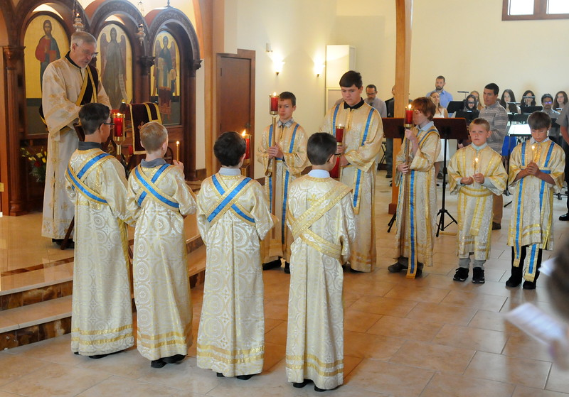 Altar boys hold candles while Deacon Mark O'Dell of Berthoud reads the Gospel passage Sunday morning, Aug. 5, 2018, during the first divine liturgy service in St. Spyridon Orthodox Church's newly renovated building. (Photo by Craig Young / Loveland Reporter-Herald)