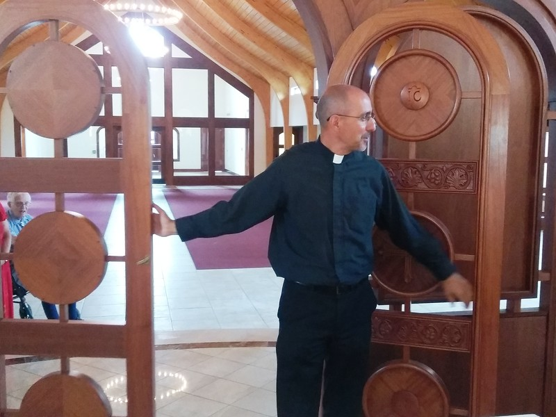 The Rev. Evan Armatas of St. Spyridon Orthodox Church demonstrates how he can open the royal doors of the icon screen that sits in front of the altar table during a public tour of the<br /> church on Aug. 2. The church, which recently opened its new sanctuary, began services there Aug. 5.  (Photo by Shelley Widhalm/ Special to the Loveland Reporter-Herald)