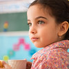 Cute hispanic girl with cup of milk at daycare