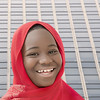 Smiling girl wearing a red headscarf in the street, twelveyears old