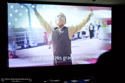 A video along with the song America the Beautiful is played on a screen as a group of approximately 40 new U.S. citizens receive their certifications of citizenship during a ceremony at the Oroville Visitors Center in Oroville, Calif. Friday July 20, 2018. (Bill Husa -- Enterprise-Record)