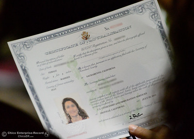 A new citizen holds her certificate of Naturalization as she and a group of approximately 40 new U.S. citizens receive their certifications of citizenship during a ceremony at the Oroville Visitors Center in Oroville, Calif. Friday July 20, 2018. This photo has had personal information removed to protect the certificate holder.  (Bill Husa -- Enterprise-Record)