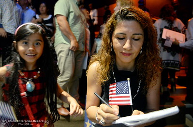 Marjan Kashefi and her 6-year-old daughter Rose Karanizadeh hold flags as a group of approximately 40 new U.S. citizens receive their certifications of citizenship during a ceremony at the Oroville Visitors Center in Oroville, Calif. Friday July 20, 2018. (Bill Husa -- Enterprise-Record)