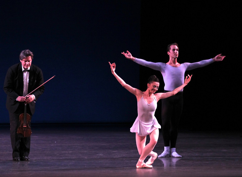 "Megan Fairchild, Jared Angle with Violinist Kurt Nikkanen, Due Concertant, New York City Ballet, September 28, 2013<br /> <br /> Watching a full-length classical ballet is easy because the plot is formulaic: boy meets girl and they either die or live happily ever after. Balanchine modernist ballets are a much more difficult task to interpret, similar to viewing an abstract painting. What is this painting about? What emotions did the artist want to convey? How do the various parts of the painting interact? What am I missing? <br /> <br /> The New York City Ballet program Balanchine Black & White presents four classic Balanchine minimalist pieces without décor, with the dancers largely in simple black and white leotards set to 20th century music. With these pieces, audience members have plenty of opportunity to attempt to find meaning and context in these master works. <br /> <br /> First up was The Four Temperaments (1946) set to music by Paul Hindemith. According to the reparatory notes, Balanchine choreographed the piece for the opening program of Ballet Society, the forerunner of New York City Ballet and is one of his earliest experimental works. ""The ballet is inspired by the medieval belief that human beings are made up of four different humors that determine a person's temperament. Each temperament was associated with one of the four classical elements (earth, air, water, and fire), which in turn were the basis of the four humors (black bile, blood, phlegm, and bile) that compose the body."" An individual's temperament is determined if one element dominates. The ballet has four variations reflecting these principles: Melancholic (gloomy), Sanguinic (headstrong and passionate), Phlegmatic (unemotional and passive), and Choleric (bad-tempered and angry). <br /> <br /> Sean Suozzi danced the morose Melancholic variation with six female dancers. He was anguished as he interacted with the other dancers, until his slow exit with an exaggerated arched back as he walked backward off the stage.<br /> <br /> Adrian Danchig-Waring danced the Phlegmatic third variation. He danced this variation quite well, with four other women. His arms flowed effortlessly, an important characteristic in this section, as there are several passages in which he bows, with arms flowing in opposition in a swimming motion. <br /> <br /> Ashley Bouder was the highlight of the piece, dancing Choleric with reckless abandon. Her solo featured precise movements on tempo featuring rapid, almost violent chaîné turns. Her jumps were powerful, forceful and with purpose. She was clearly on a mission to capture the essence of a bad-tempered angry individual.<br /> <br /> The second piece was Episodes (1959) set to music from Anton von Webern. According to the notes, Episodes was made in honor of von Webern by New York City Ballet and Martha Graham and her company. The piece opens with four couples led by Abi Stafford and Sean Suozzi. There is much action here to discordant music; the technique is classical, with flexed feet, off balance lunges, overly arched backs every now and then to remind that is a neoclassical piece. <br /> <br /> I enjoyed the pas de deux by Teresa Reichlen and Ask la Cour. Reichlen was in a white leotard while la Cour in black with a spotlight highlighting the color contrasts. The interplay during the tense pas de deux was dramatic. I also enjoyed Sara Mearns and Jonathan Stafford as they danced to the more soothing music of Ricercata in six voices from Bach's ""Musical Offering."" <br /> <br /> My favorite of the evening was Duo Concertant (1972) with Megan Fairchild and Jared Angle. Violinist Kurt Nikkanen and pianist Susan Walters were on stage as the curtain opened, playing the Stravinsky piece from 1931 as Megan and Jared stood behind them listening. Here the musicians are not just unobserved partners, they are part of the dance as the dancers frequently acknowledge them and stop to listen to the beautiful music. They start their dance side-by-side moving in opposition with mechanical movements dominated by intricate, fast footwork. Jared's dance was fast featuring quick single tours in succession. The piece is cheerful, joyful, and inspiring. <br /> <br /> In the end, the stage goes dark and the music slows; they are illumined by a dim light; they embrace; she runs off-stage; he is alone and lost; she returns and their hands embrace, highlighted by a spotlight in a dramatic climax. <br /> <br /> The final piece was Symphony in Three Movements, another 1972 piece set to Stravinsky. Daniel Ulbricht and Ana Sophia Scheller were exciting in the opening movement. Scheller was very limber, almost kicking herself in the head on an arabesque. Daniel is one of my favorites and I love watching his controlled and high double tours. The opening segment had a lot of dancers on stage as they darted in and out of the action. The second movement featured a nice pas de deux from Sterling Hyltin and Amar Ramasar. <br /> <br /> These pieces are complicated and nuanced; you could see these 10 times and pick up something new that you hadn't seen before in the 11th viewing. I was absorbed in the Saturday performance but there was so much that I missed. I look forward to seeing it again Friday night for more insight on Balanchine's abstract canvas."