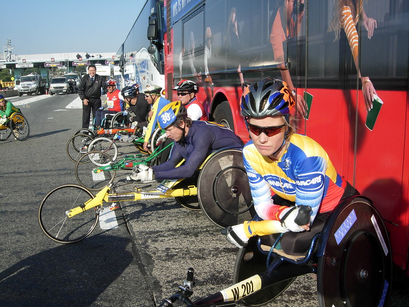 Wheelchair racers use race buses for shelter from the wind while waiting to begin their race.