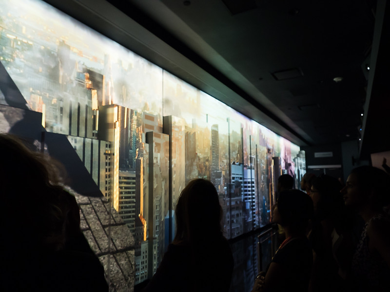 You step out of the elevator into a video presentation which opens up to a view to the city.