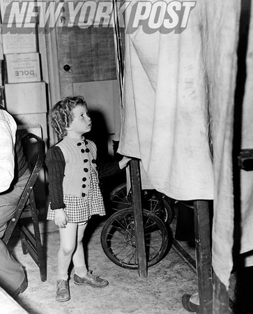 Eileen Liss -- Waits outside Brooklyn registry booth while her mother selects her political party. 1956