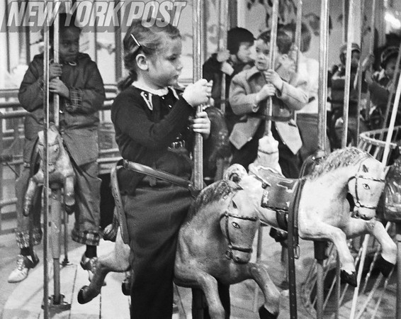 Children enjoy the Carousel while their parents shop for Christmas. 1955