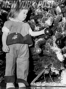 Young girl admires her Christmas Tree and it's decorations. 1960