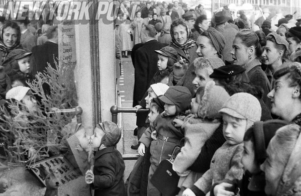 Christmas shoppers crowd around to see New York City's Christmas window displays. 1955