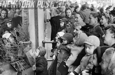 Christmas shoppers crowd around to see New York City's Christmas window displays. 1955