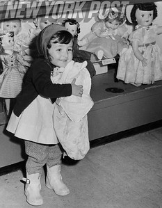 This young girl found her favorite doll while Christmas shopping. 1957