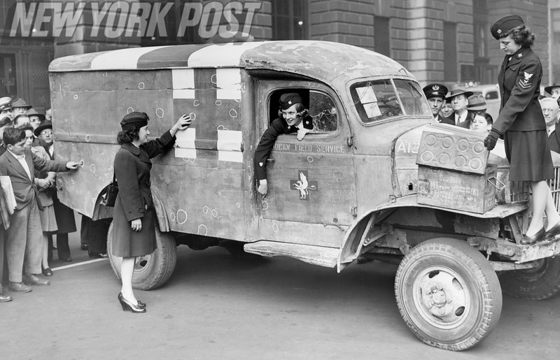 American Red Cross workers show off their International ambulance and it's damage. 1945