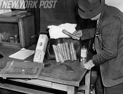 Detective examines explosives found on Louis Friedman. 1938