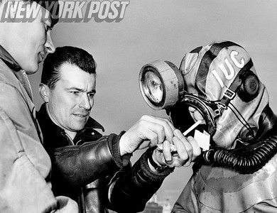 Deep Sea Diver comes up for a smoke after inspecting FDR Drive from the East River. 1962