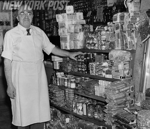 Local Grocery Store owner in Manhattan with a display of goods.