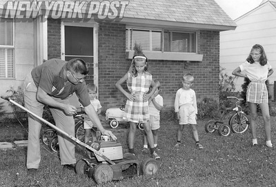 Manhattan Family gathers around to see the gas lawnmower in action.