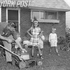 Manhattan Family gathers around to see the gas lawnmower in action