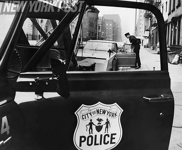 New York City policeman readies a car for tow in Manhattan. 1967