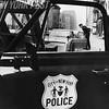 New York City policeman readies a car for tow in Manhattan. 1967