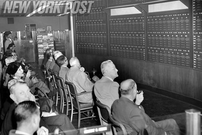 Concerned traders and investors watch the Stock Market board in New York City.