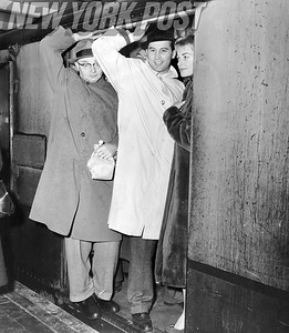 Last minute riders on the train at Flushing Station hold on tight. 1957