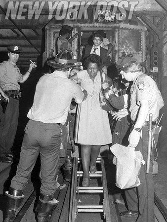 Subway patrons are rescued from a fire on the train by NYC firefighters. 1979