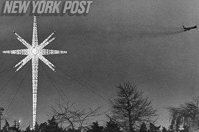 Airliner zooms out of sight above Kennedy International Airport and the Star of Christmas. 1966