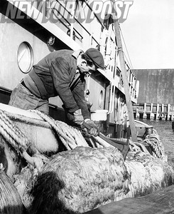 Jim Williams takes care of his tugboat on the coldest day of the year. December 1960
