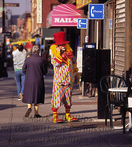 Bubbles the clown talks on a pay phone on Smith Street in Brooklyn on his way to perform at a kids birthday party