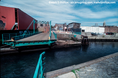 The Carroll Street Bridge stands open over the Gowanus Canal with very little around it except empty warehouses in 1996. In the distance at right are the Twin Towers and the steeple of St Agnes.