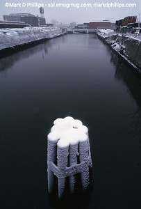 Snow on a pylon in the Gowanus Canal looking toward the Carroll Street bridge from Union Street. the 1.7 mile long canal is currently in an EPA Superfund cleanup plan that is estimated to be over $1.5 billion, and the entire project won't be completed until mid-2023. The Gowanus Canal is located in one of the densest population centers in America.