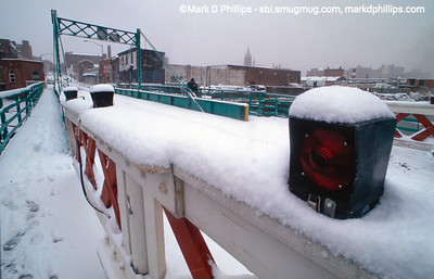 """Carroll Street Bridge in the snow over the Gowanus Canal in Brooklyn, NY. In 1889, the Carroll Street Retractable Bridge opened and today is one of only four retractable bridge's remaining in the world.  Built at a cost of $36,742.58, the beloved bridge supports a 17 foot wide roadway and two 4.5 foot sidewalks that are pulled onto the shore on tracks via a cable and pulley system. Landmarked in 1987, the bridge was built to allow horse and wagons to cross the increasingly busy waterway, and still features a sign stating """"Any Person Driving over this Bridge Faster than a Walk will be Subject to a Penalty of Five Dollars For Each Offence."""""""