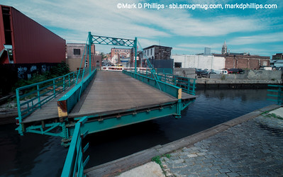 """The Carroll Street Bridge stands open over the Gowanus Canal with very little around it except empty warehouses in 1996. In the distance at right are the Twin Towers and the steeple of St Agnes. In 1889, the Carroll Street Retractable Bridge opened and today is one of only four retractable bridge's remaining in the world.  Built at a cost of $36,742.58, the beloved bridge supports a 17 foot wide roadway and two 4.5 foot sidewalks that are pulled onto the shore on tracks via a cable and pulley system. Landmarked in 1987, the bridge was built to allow horse and wagons to cross the increasingly busy waterway, and still features a sign stating """"Any Person Driving over this Bridge Faster than a Walk will be Subject to a Penalty of Five Dollars For Each Offence."""""""