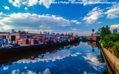 Clouds reflect in the water of the Gowanus Canal looking north with the Twin Towers peeking above the shoreline. The wall reflected in the water has no graffiti in 1989 and downtown Brooklyn has not risen to its new heights.