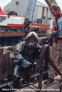 Diver climbs ladder out of the Gowanus Canal completely covered in Black goo during the city-led 1999 cleanup effort that involved repairs to the flushing tunnel and a partial dredging at the head of the waterway. The results were immediate with an increase in fish and wildlife. The divers had challenging conditions, coming out covered in oil and tar and working conditions with no visibility underwater.
