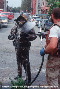 Diver out of the Gowanus Canal completely covered in Black goo being hosed off. during the city-led 1999 cleanup effort that involved repairs to the flushing tunnel and a partial dredging at the head of the waterway. The results were immediate with an increase in fish and wildlife. The divers had challenging conditions, coming out covered in oil and tar and working conditions with no visibility underwater.