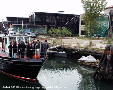 The Brooklyn Center for the Urban Environment offers first boat cruise on the Gowanus Canal in 1997 with executive director John Muir. They found dissolved oxygen at just 2.8 ppm (need 5ppm for fish life) and light can penetrate only 2 feet (need 6 for plant life). On board a tour in 2000 was Buddy Scotto, NY Assemblywomen Joan Millman, and US Congresswoman Nydia Valesquez as they pass David Lefkowitz's property beside the Carroll Street Bridge.